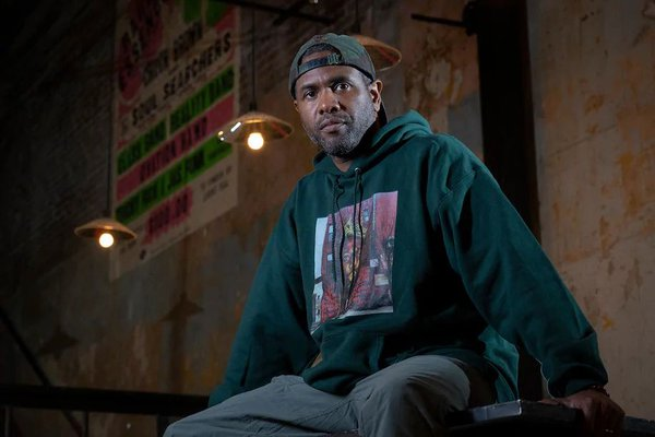 photo of playwright seated on stage wearing a hooded sweat shirt bearing the portrait of Notorious B.I.G.