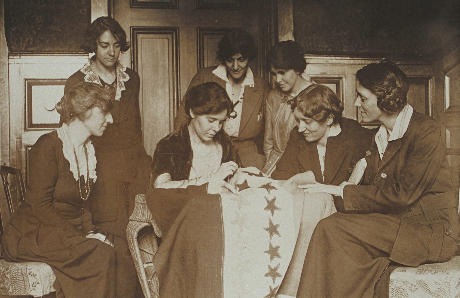 women assembled at a table sewing a flag