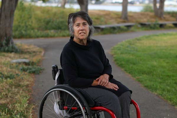 portrait of a person seated in a wheelchair with landscape in background
