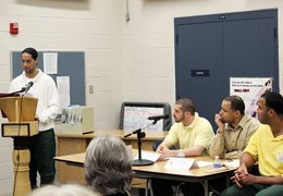 An inmate at Five Points Correctional Facility presenting from a lectern in his college class.