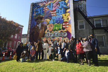 people assembled in front of mural