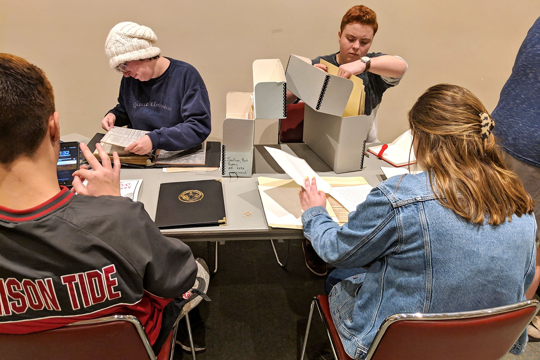 students at table with archival boxes