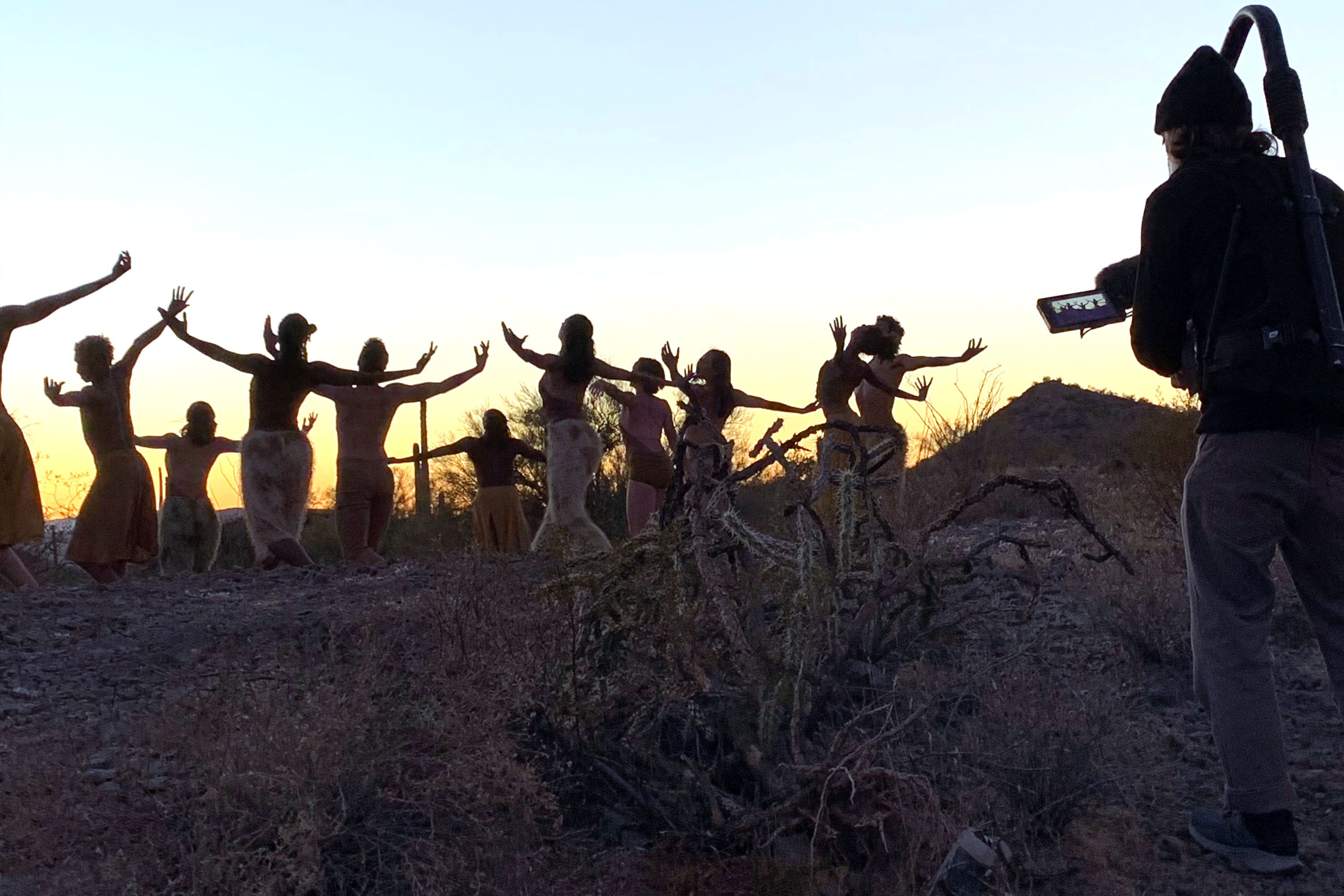 dancers outside in desert with videographer