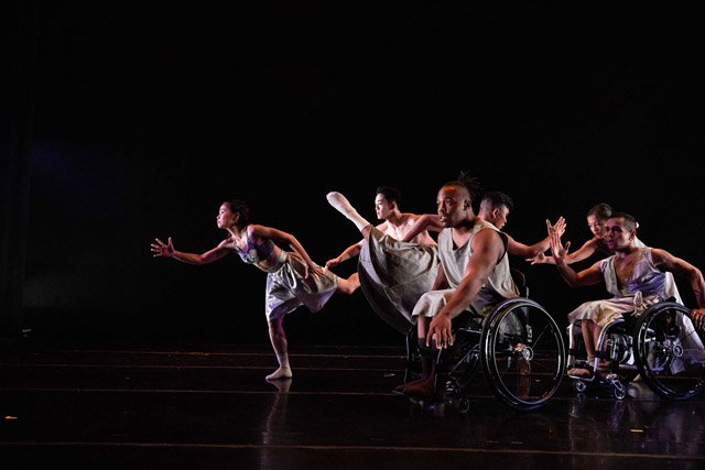 dancers with a range of physical abilities performing on a dark stage