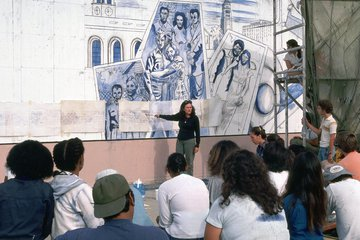 muralist and community members in front of a work in process