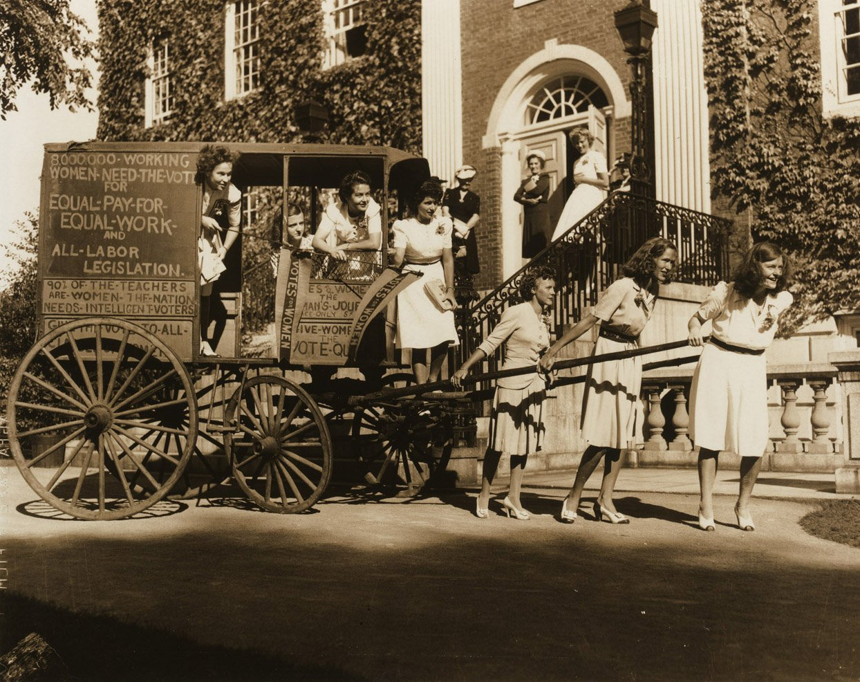 women surrounded by an antique cart in front of a university building