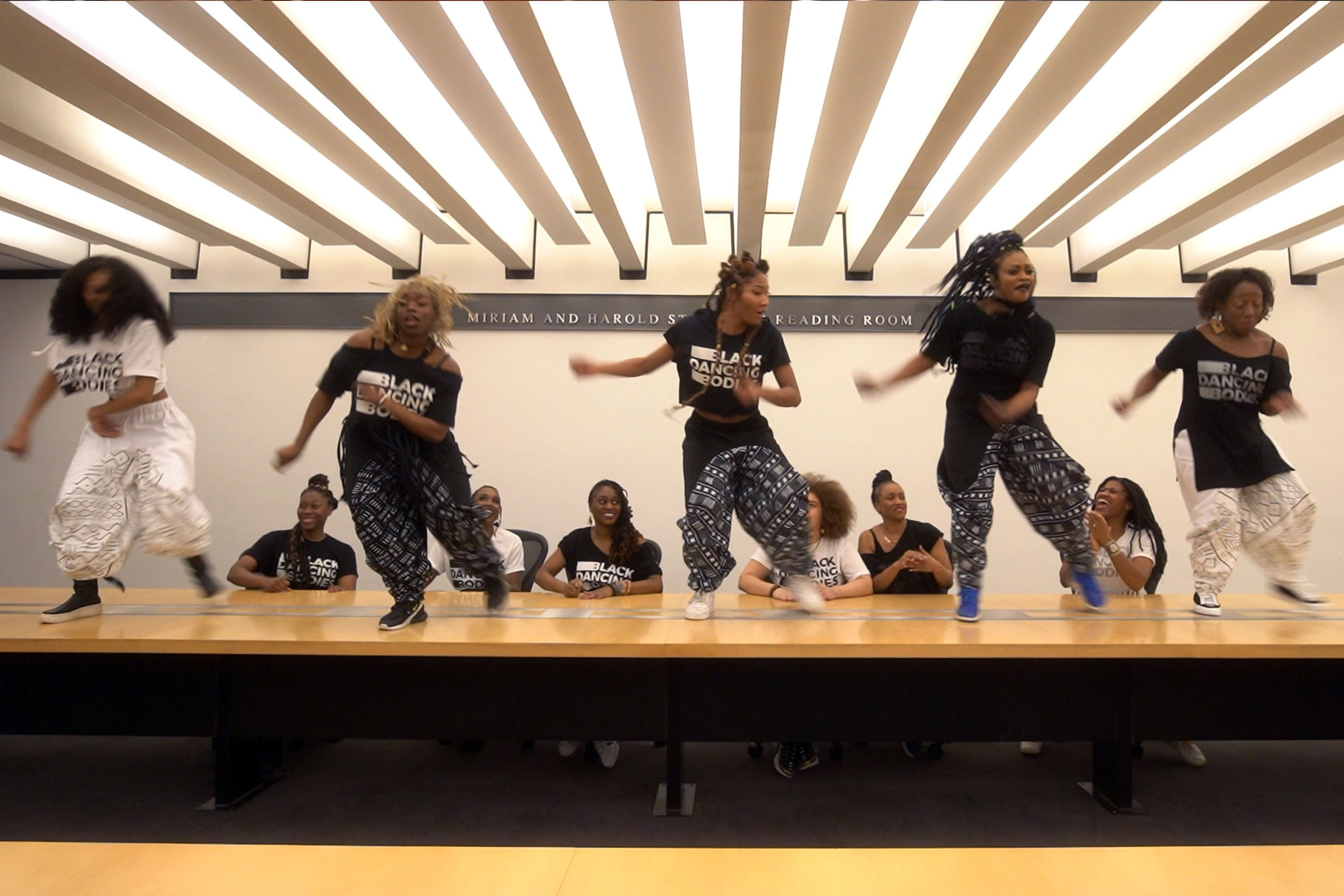 dancers performing on conference room table