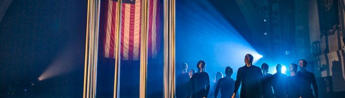 performers on stage with an American flag behind a cage of bars
