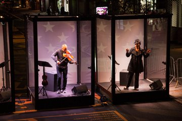 two actors/musicians on stage, inside individual glass booths