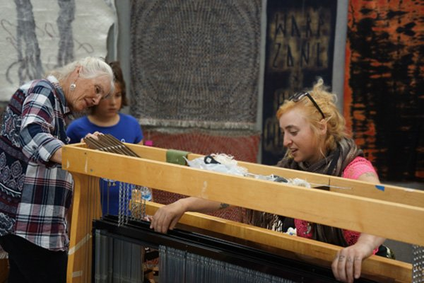 Two visitors and a fiber artist at a loom.