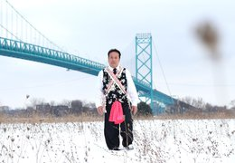 man standing in traditional dress in a snowy field with a bridge in the background