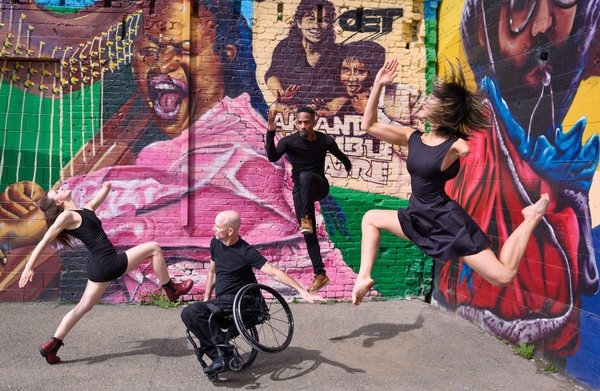 Dancers perform in front of a mural